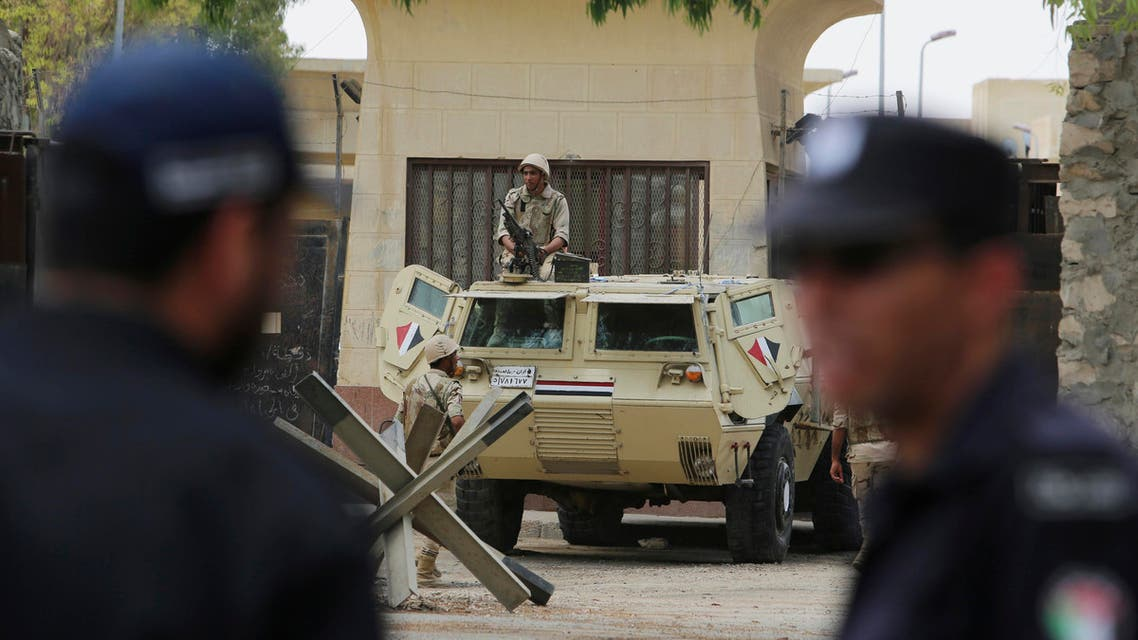 Hamas security officers, front, stand guard as Egyptian soldiers are posted in the Egyptian side of the Rafah border crossing, as seen from Rafah in the southern Gaza Strip, Tuesday, May 26, 2015.