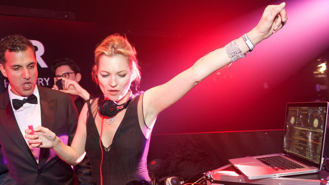 Kate Moss, right, plays DJ at the inaugural amfAR Hong Kong gala on Saturday, March 14, 2015 in Hong Kong. (AP)