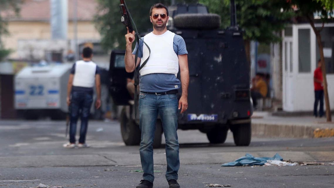A Turkish police officer, wearing a protective jacket and holding a weapon secures an area in Diyarbakir, southeastern Turkey, Tuesday, June 9, 2015.