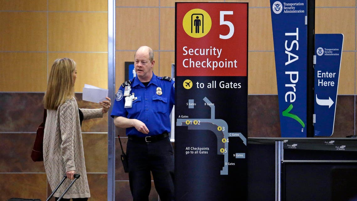 In this photo taken Tuesday, March 24, 2015, a passenger shows a boarding pass to a TSA agent at a security check-point at Seattle-Tacoma International Airport in SeaTac, Wash. (AP Photo/Elaine Thompson)