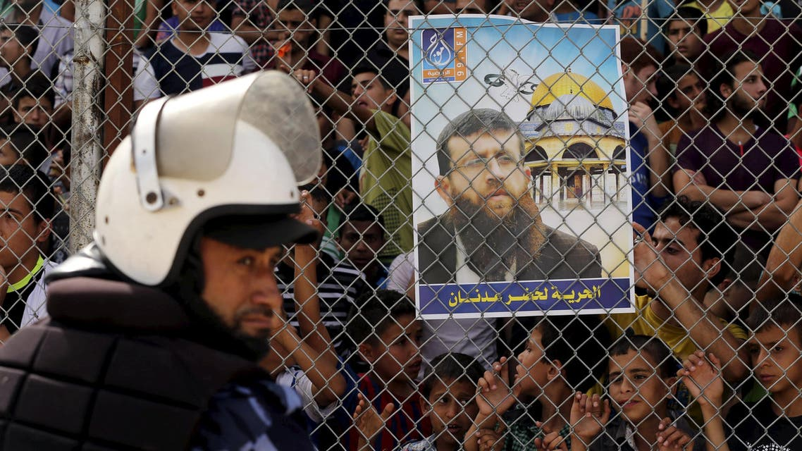 A Palestinian policeman loyal to Hamas stands guard as spectators stand behind a fence and hold a poster depicting Palestinian prisoner Khader Adnan, who is being held in an Israeli jail, as they watch the Gaza Strip Cup final soccer match between Ittihad Shejaiya and Khadamat Rafah in Gaza City June 7, 2015. REUTERS