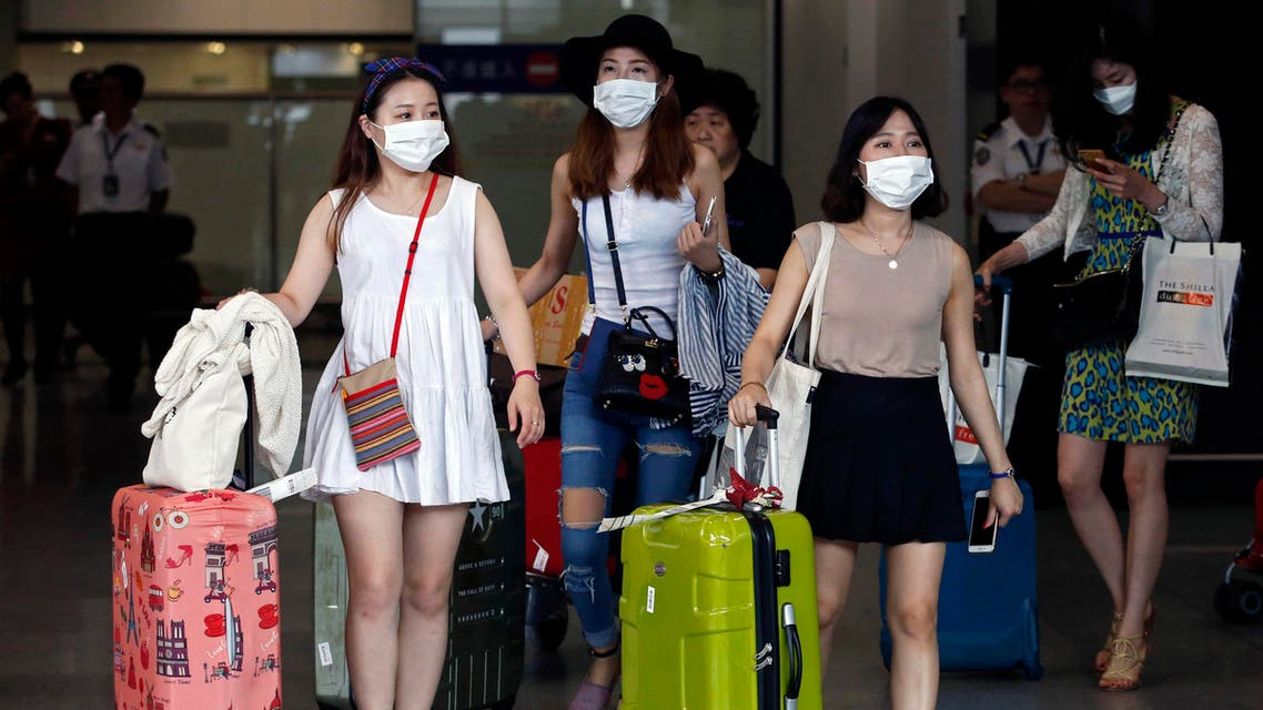 Passengers flying from Seoul, South Korea, wear masks as a precaution against MERS, Middle East Respiratory Syndrome, as they arrive at Hong Kong Airport Tuesday, June 9, 2015. (AP)