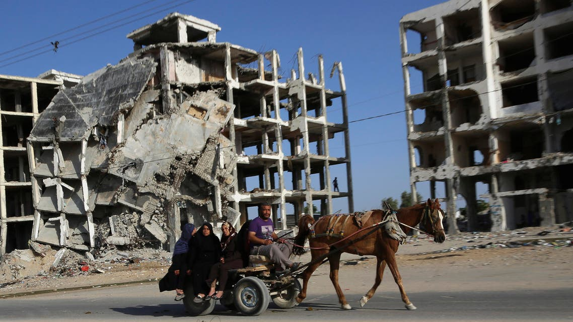 Palestinian family members ride a horse cart as they pass apartment buildings that were destroyed in the last summer's Israel-Hamas war, in the residential neighborhood of Beit Lahiya in the northern Gaza Strip, Tuesday, June 2, 2015. AP