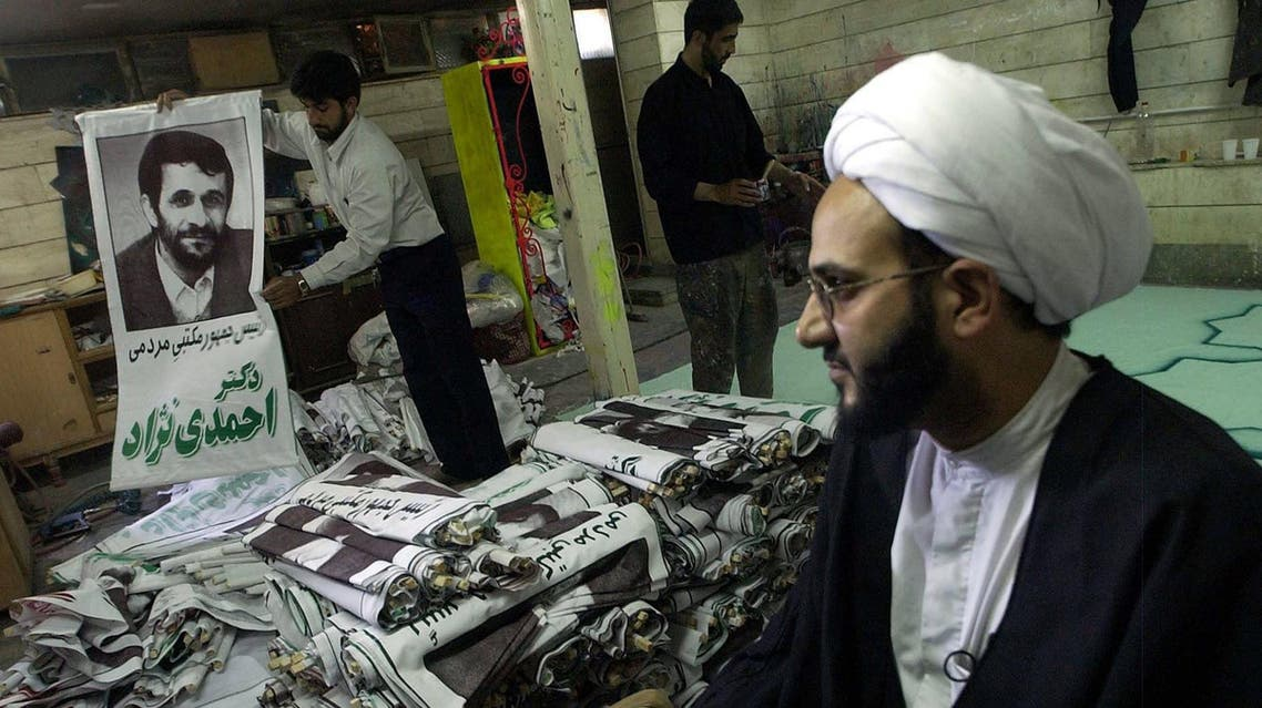 Iranian cleric Mehdi Aghajani, right, looks on as Mohammad Hossein Pour, center, and an unidentified person prepare Tehran's Mayor and presidential candidate Mahmoud Ahmadinejad's posters on the last day of the election campaign in Isfahan, Iran Wednesday June 22, 2005. AP