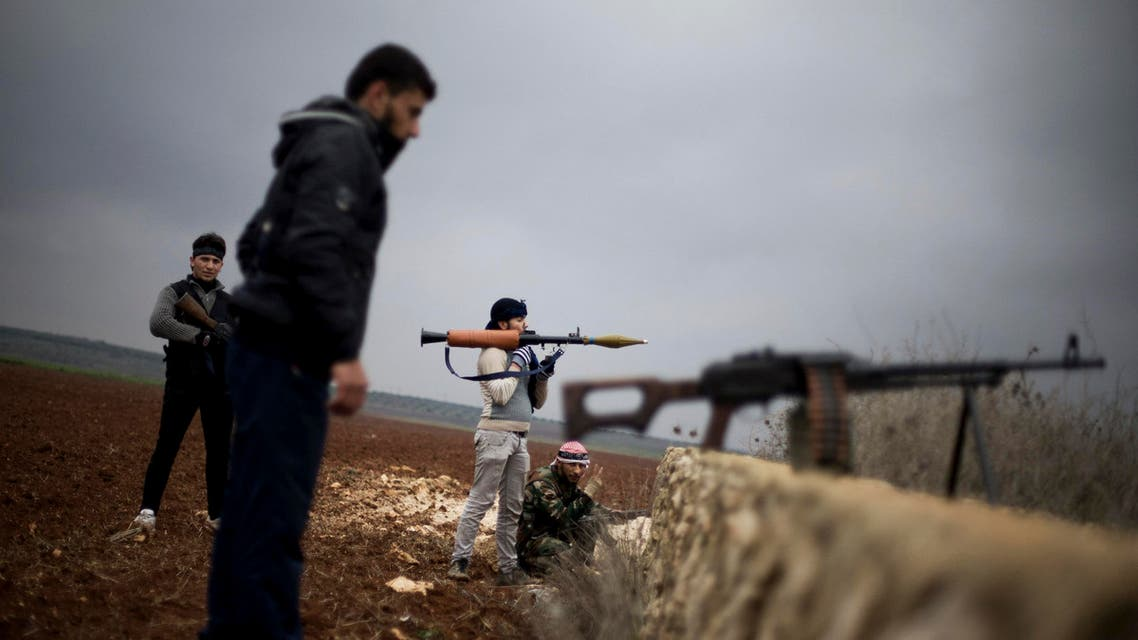 In this Dec. 10, 2012, Free Syrian Army fighters take their positions, close to a military base, near Azaz, Syria. (File Photo: AP)