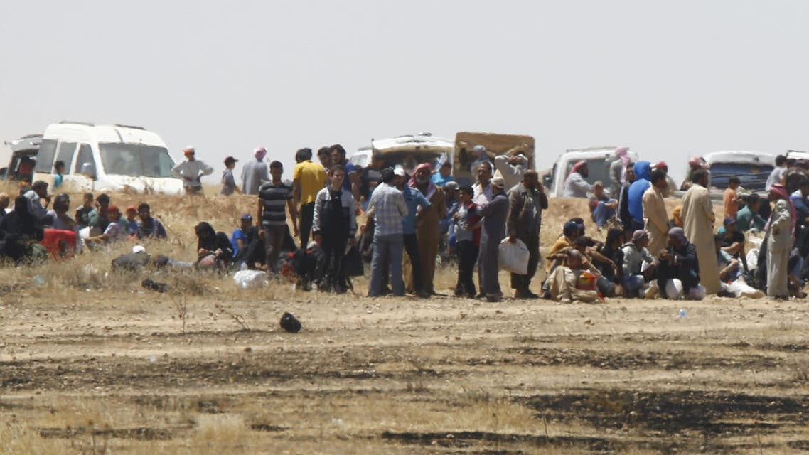 Syrian refugees wait near the border fences as they are pictured from the Turkish side of the border, near Akcakale in Sanliurfa province, Turkey, June 11, 2015. (Reuters)