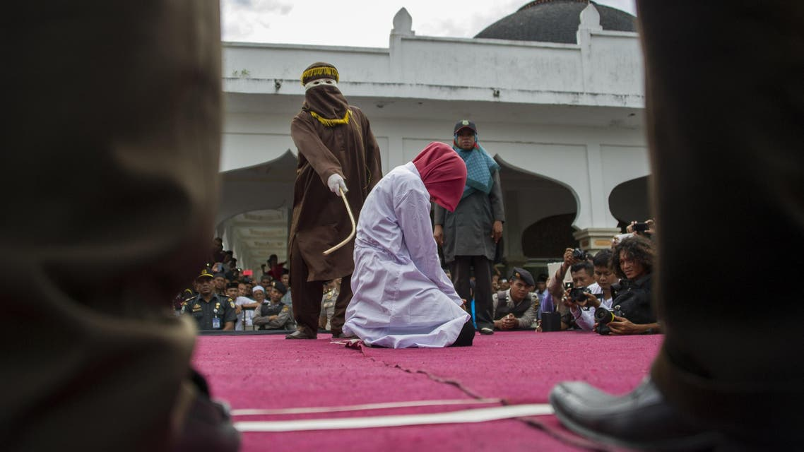 """An Acehnese woman convicted for """"immoral acts"""" is lashed by a hooded local government officer during a public caning at a square in Banda Aceh, Aceh province, on June 12, 2015. AFP PHOTO / Chaideer MAHYUDDIN"""