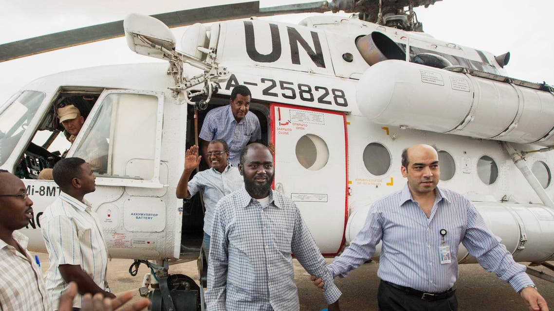 A member of the joint U.N. African Union Mission in Darfur (UNAMID), right, escorts three freed humanitarian workers out of a U.N. helicopter as they landed in Darfur, July 19, 2014. (File Photo: AP)