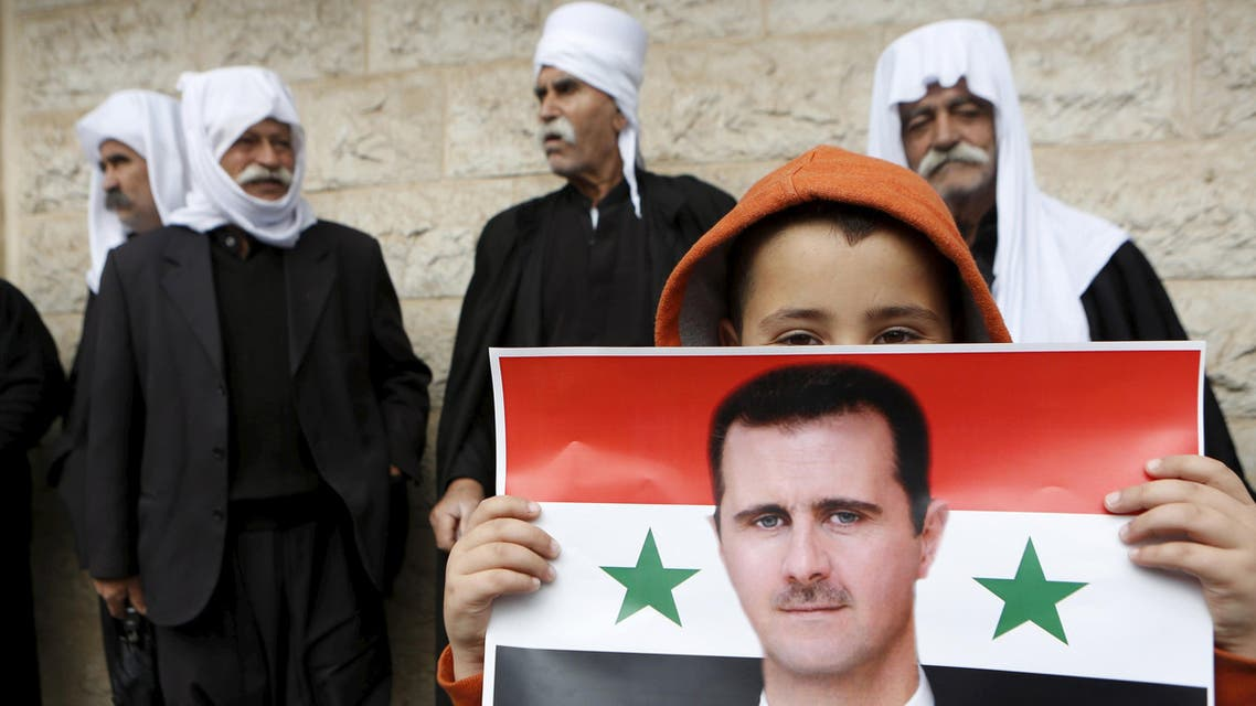 A picture shows a boy holding a flag with the image of Syria's President Assad during a rally in a Druze village on the Golan Heights. (File Photo: Reuters)