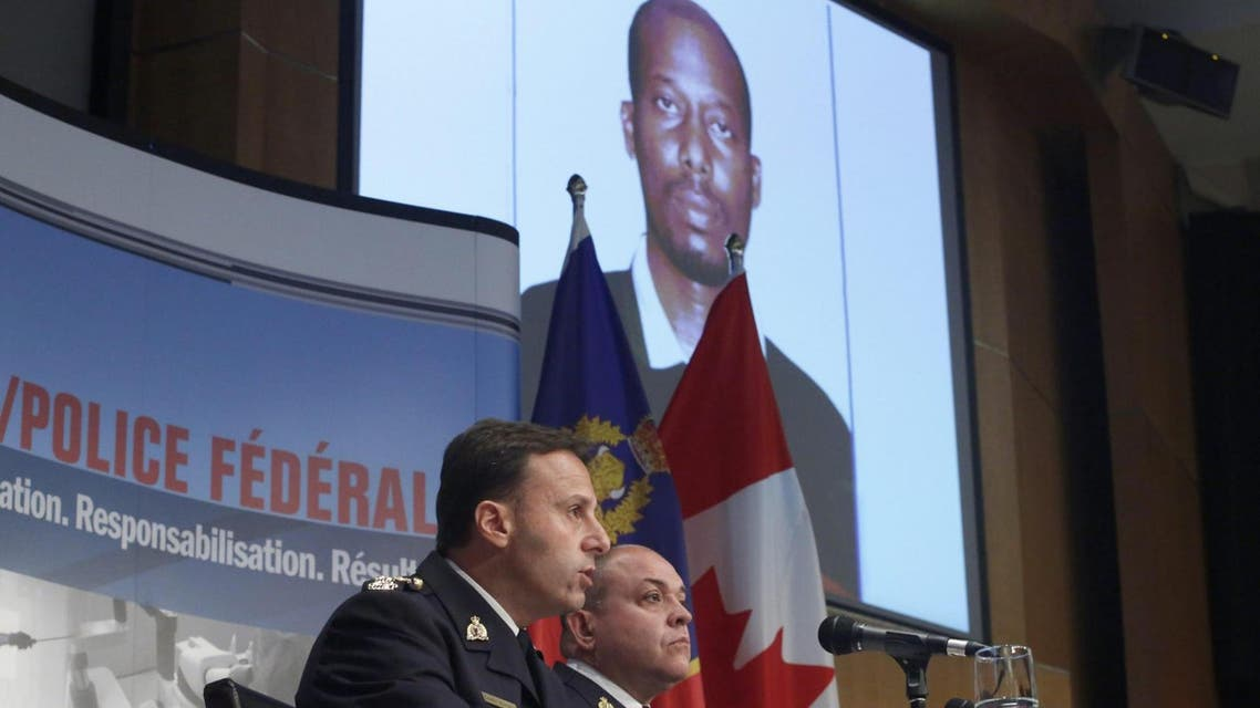 Royal Canadian mounted police assistant commissioner James Malizia, left, and inspector Paul Mellon announced the arrest on Friday of Ali Omar Ader, shown on screen. (AP)