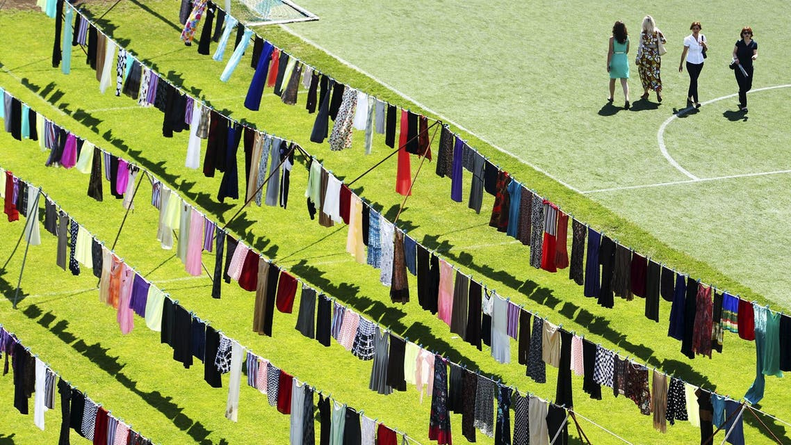 """Dresses and skirts are seen hanging inside a stadium, in an art exhibition titled """"Thinking of You"""" by Kosovo-born, London-based artist Alketa Xhafa-Mripa, in Pristina June 12, 2015. (Reuters)"""