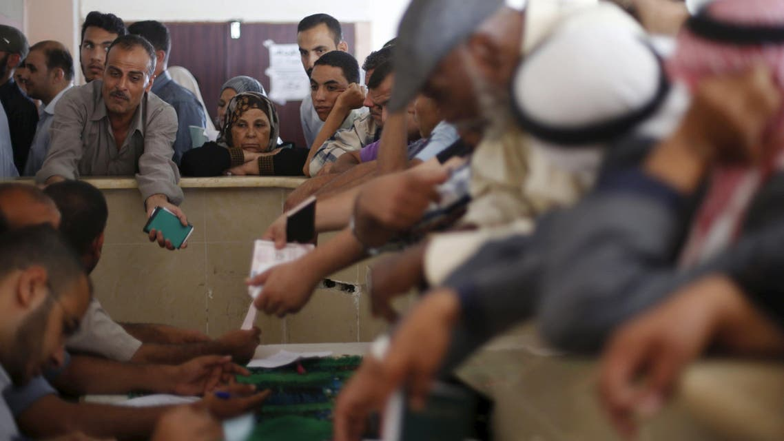 Palestinians ask for travel permits to cross into Egypt, at the Rafah border crossing between Egypt and the southern Gaza Strip, June 13, 2015.