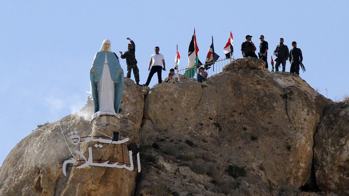Members of the Syrian National Defence Forces (NDF) stand behind a statue of Virgin Mary perched on the cliffs overlooking the ancient Christian town of Maalula, 56 kilometers northeast of the Syrian capital Damascus, on June 13, 2015. (AFP)