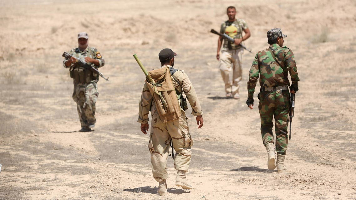 Fighters from the Badr Brigades Shiite militia patrol at the front line, in Kessarrat, located (70 kilometers) north west of Baghdad, Iraq, Friday, June 12, 2015.