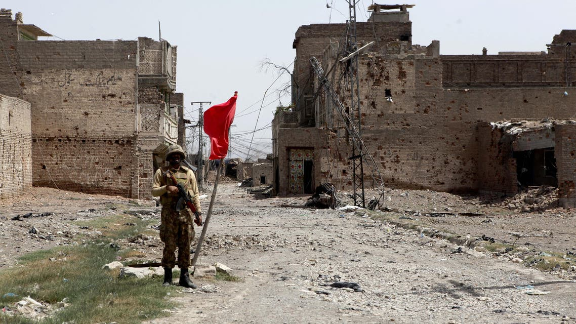 In this photo taken on Wednesday, July 9, 2014, a Pakistan army soldier stands guard in the Miran Shah bazaar after driving out militants in North Waziristan, in Miran Shah, Pakistan.