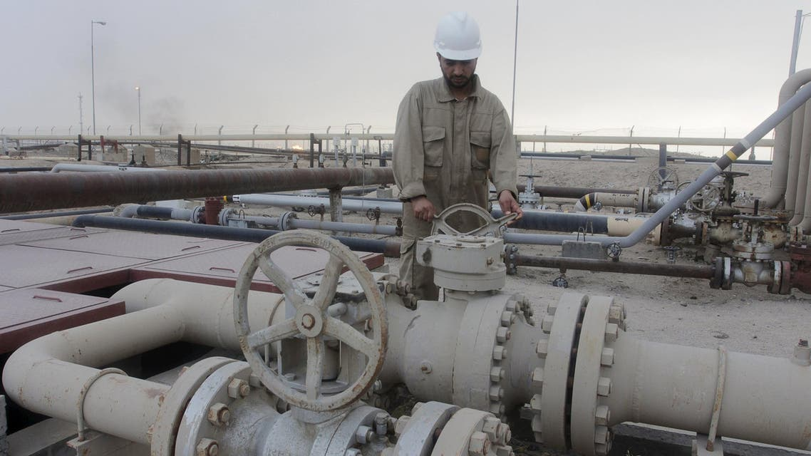 A worker checks the valve of an oil pipe at Rumaila oilfield in Basra, southeast of Baghdad, Iraq June 6, 2015. REUTERS