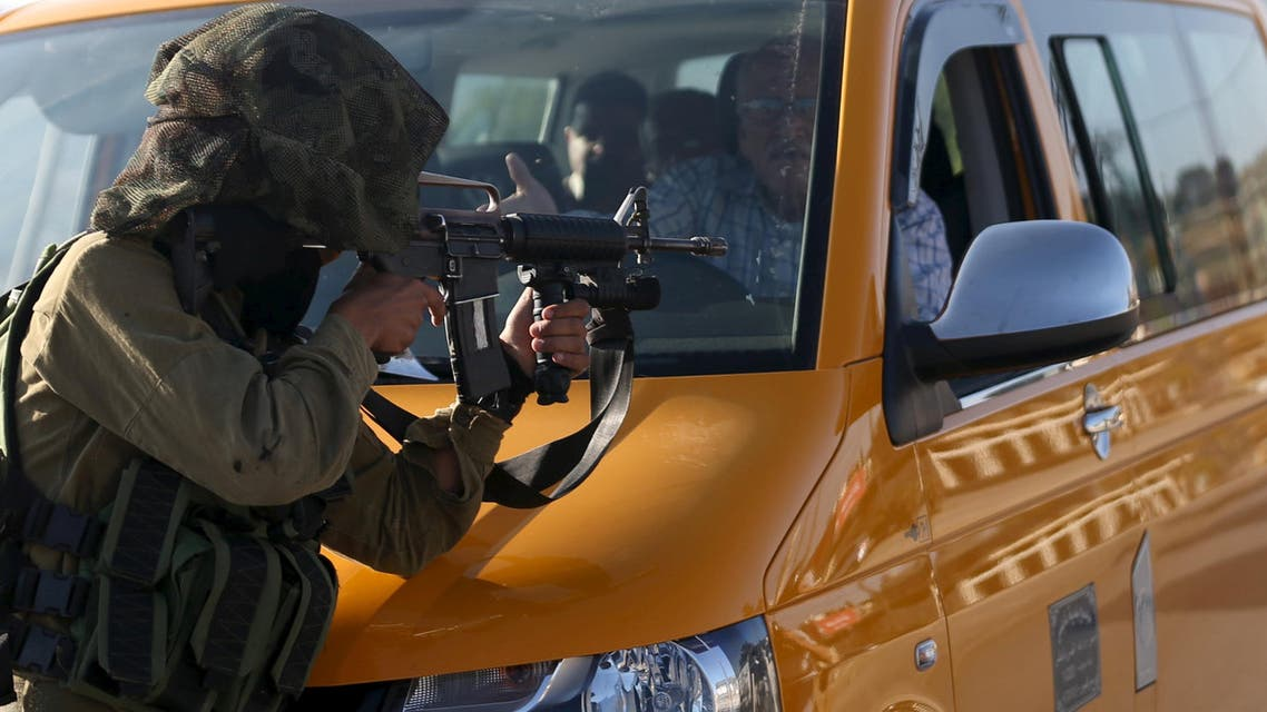 A driver stops his vehicle in front of an Israeli soldier who is aiming his weapon at demonstrators during clashes with Palestinians following a protest against Jewish settlements, in Jalazoun refugee camp, near the West Bank city of Ramallah June 12, 2015. (Reuters)