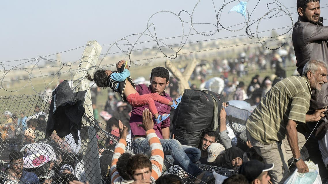 A man carries a girl as Syrians fleeing the war pass through broken down border fences to enter Turkish territory illegally, near the Turkish Akcakale border crossing in the southeastern Sanliurfa province, on June 14, 2015. AFP