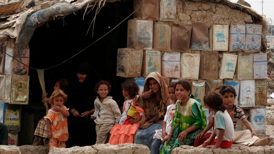 A family group is seen outside their home, which is constructed with mud and tin cans in the Dora neighborhood of Baghdad, Iraq, on Monday, Sept. 8, 2008. (AP Photo/ Loay Hameed)