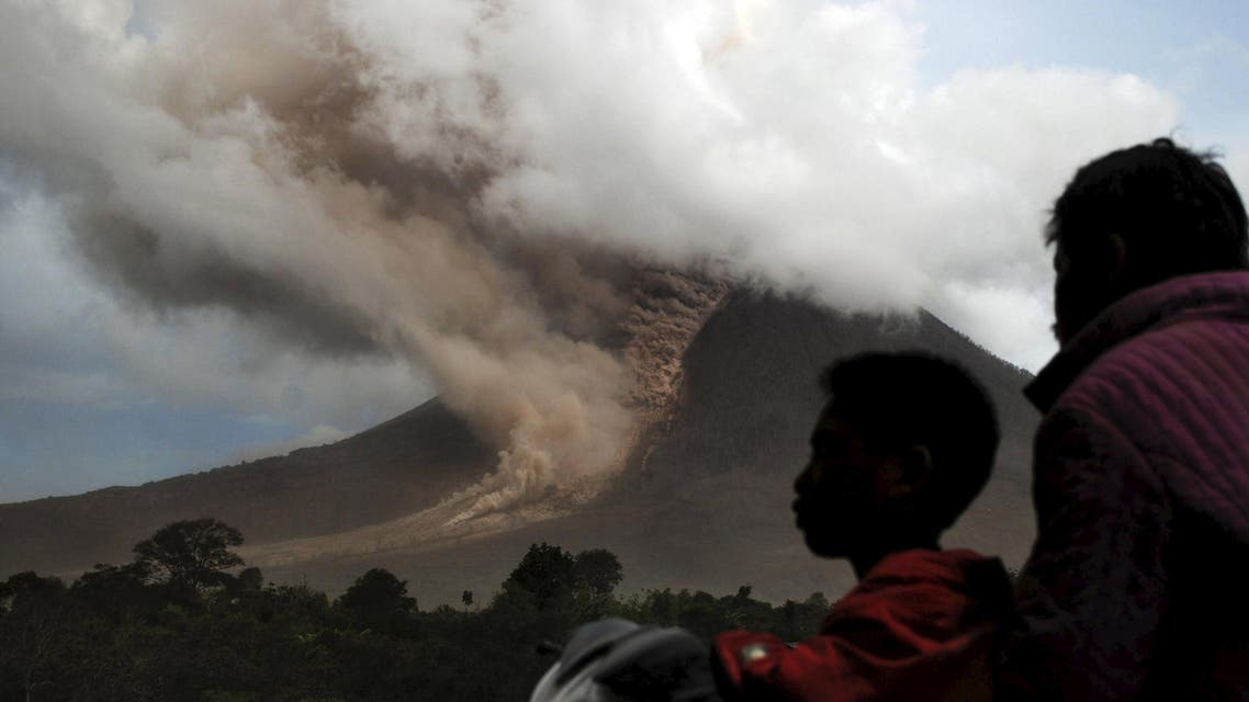 Residents sit on their motorcycle as they watch an eruption at Mount Sinabung, in Namanteran village in Karo Regency, Indonesia's North Sumatra province, June 14, 2015 in this photo taken by Antara Foto. Reuters