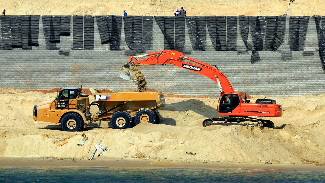Bulldozers and trucks work on a new section of the Suez canal during a media tour in Ismailia, Egypt, Saturday, June 13, 2015. Work on a parallel waterway to allow two-way traffic on Egypt's Suez Canal will be finished in time to allow ships to transit for a gala inauguration at the key trade route on Aug. 6, officials said Saturday. President Abdel-Fattah el-Sissi ordered the new waterway to be dug in a single year, saying that the urgency of Egypt's economic situation meant the project could not wait for an originally planned three-year timetable. (AP Photo/Hassan Ammar)