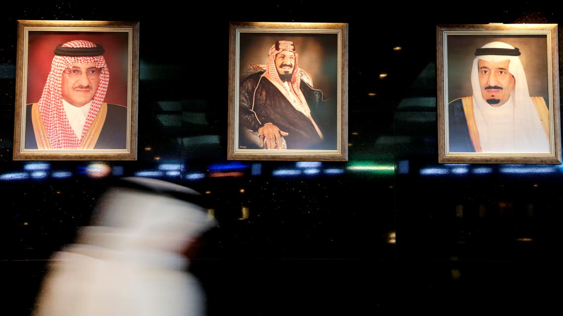 A man walks past portraits of Saudi leaders at the Tadawul Saudi Stock Exchange, in Riyadh, Saudi Arabia, Monday, June 15, 2015. Saudi Arabia's stock market, valued at $585 billion, opened up to direct foreign investment for the first time Monday, as the kingdom seeks an economic boost amid low global oil prices. (AP Photo/Hasan Jamali)