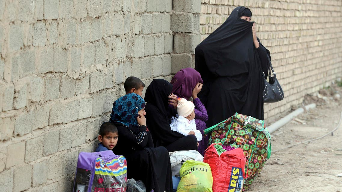In this file photo taken Wednesday, March 18, 2015, internally displaced people who fled from Tikrit, Iraq, because they feared Islamic State militants settle at a refugee camp outside Baghdad, Iraq. AP