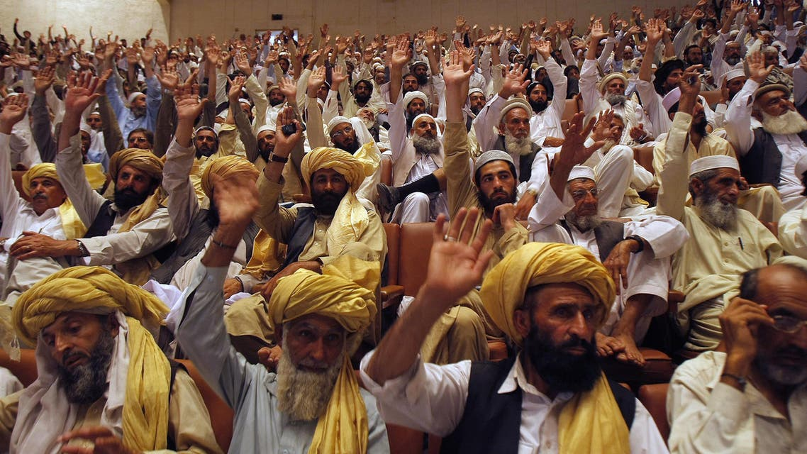 Pakistani tribal elders raise their hands in favor of Islamic laws in Pakistan's tribal areas, during a peace jirga or grand meeting in Peshawar, Pakistan, Thursday, May 1, 2014. AP
