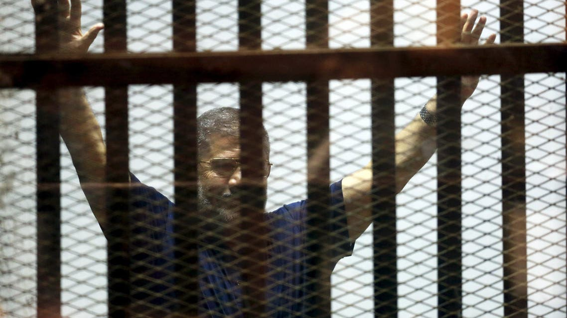 Former Egyptian President Mohamed Mursi waves during his appearance in court on the outskirts of Cairo, Egypt. (Reuters)
