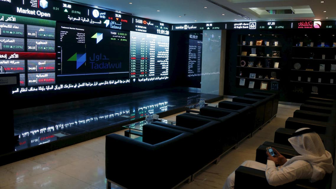 A trader uses his mobile as he monitors screens displaying stock information at the Saudi Stock Exchange (Tadawul) in Riyadh June 15, 2015. (Reuters)