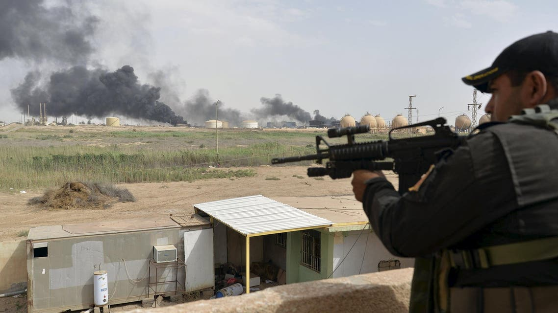 A member from the Iraqi security forces guards as smoke rises from Baiji oil refinery, north of Baghdad, Iraq May 26, 2015. REUTERS