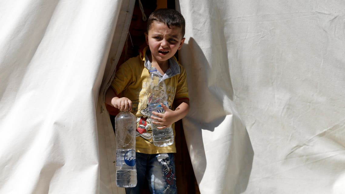 A boy holds two bottles of water as he leaves a tent at a refugee and migrant camp in the village of Moria on the northeastern Greek island of Lesvos on Wednesday, June 17, 2015. AP