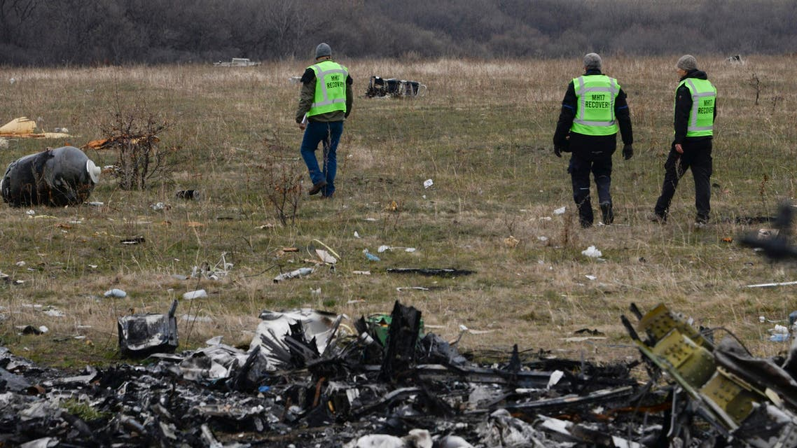 MH17 flight recovery team members examine one of the areas of the Malaysia Airlines Flight 17 plane crash in the village of Hrabove, Donetsk region, eastern Ukraine Tuesday, Nov. 11, 2014. (AP Photo/Mstyslan Chernov)