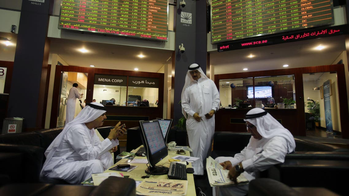 In this Thursday, Oct. 2, 2014 file photo, Emirati traders check the stocks of Emaar Malls on the screen at the Dubai Financial Market in United Arab Emirates. (AP)