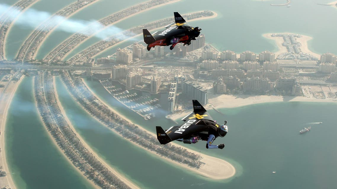An aerial view taken from a sea plane shows Swiss pilot and original Jetman Yves Rossy (front) and Vince Reffett flying over Dubai's Palm Island, Dubai, United Arab Emirates May 12, 2015.