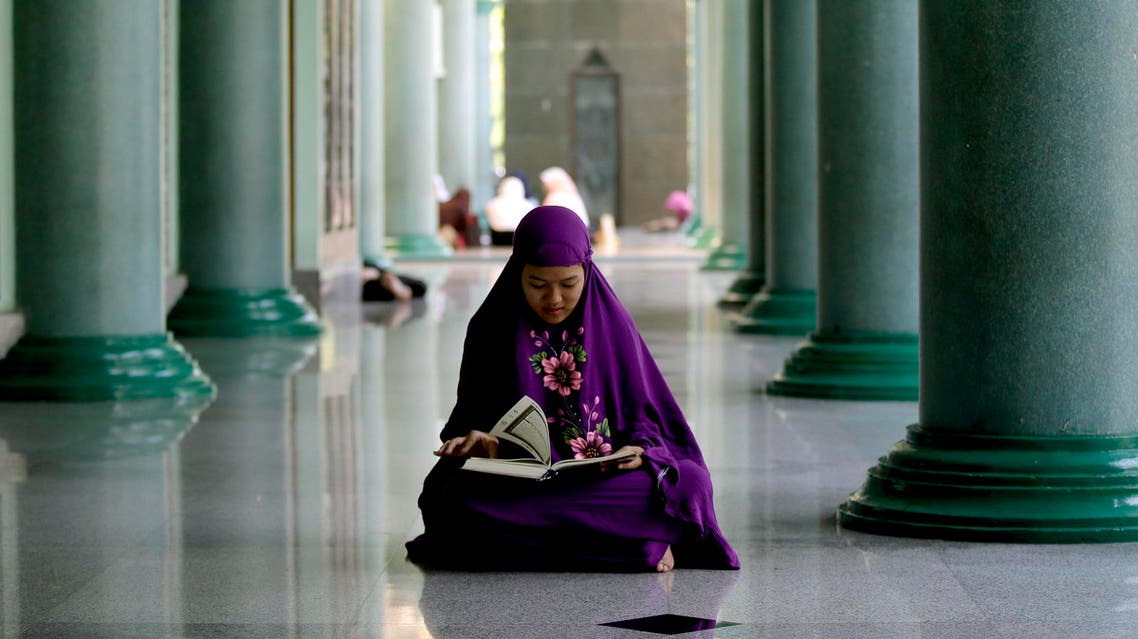 A Muslim woman reads the Quran during the first day of the fasting month of Ramadan at a Mosque on the outskirts of Jakarta, Indonesia, Thursday, June 18,2015.  (AP)