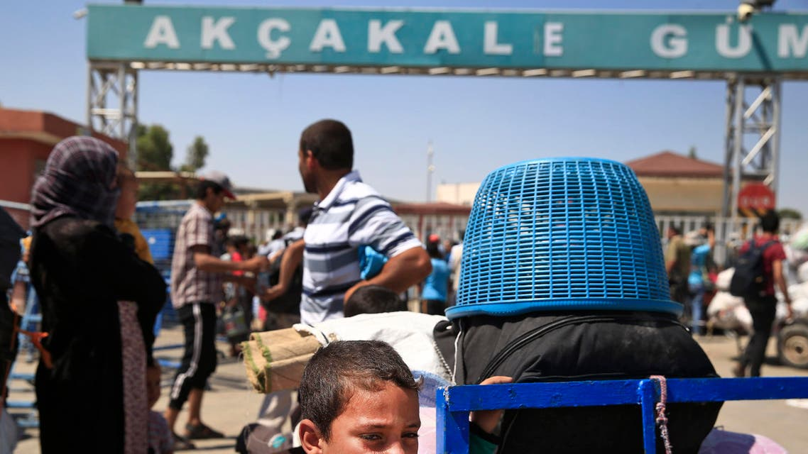 Syrians wait with their belongings to cross back to the border town of Tal Abyad in Syria from Turkey, at the border crossing in Akcakale, southeastern Turkey, Wednesday, June 17, 2015. Some hundreds of Syrians are returning to Tal Abyad from Turkey a day after Kurdish fighters evicted Islamic State group fighters from the area. The Kurdish advance caused the displacement of about 23,000 people who fled into Turkey from the fighting in the past two weeks, according to the UNHCR. (AP Photo/Lefteris Pitarakis)