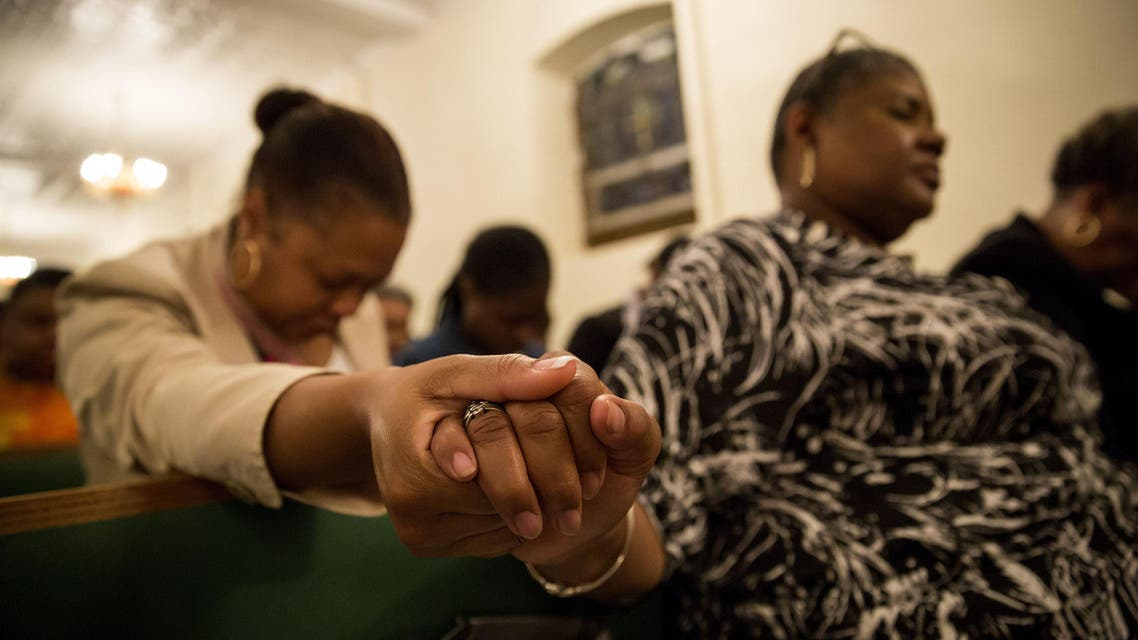 Mourners hold a prayer vigil for the nine victims of last night's shooting at the historic Emanuel African Methodist Episcopal Church in Charleston, South Carolina June 18, 2015 at the First African Methodist Episcopal Church: Bethel in the Harlem neighborhood of New York City. AFP