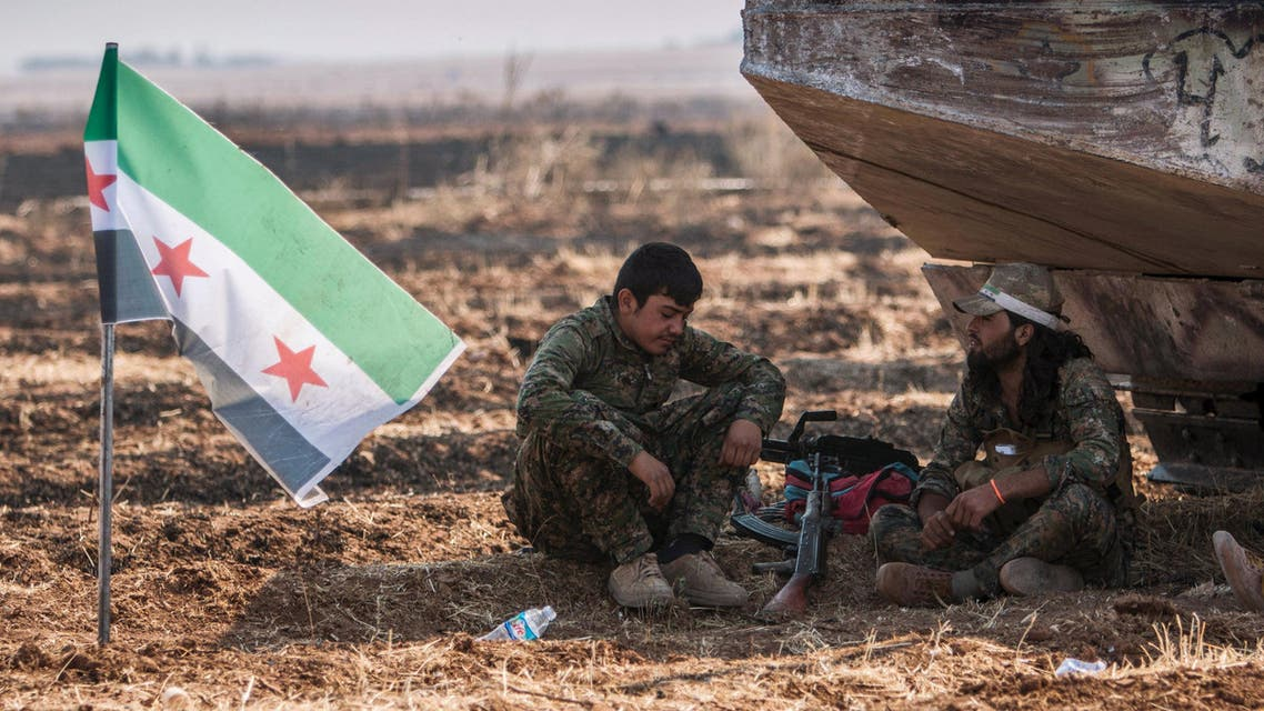 Fighters from the Free Syrian Army's Al-Tahrir Brigade, rest near their flag on the eastern outskirts of the city of Tel Abyad of Raqqa governorate after they said they took control of the area June 15, 2015. Reuters