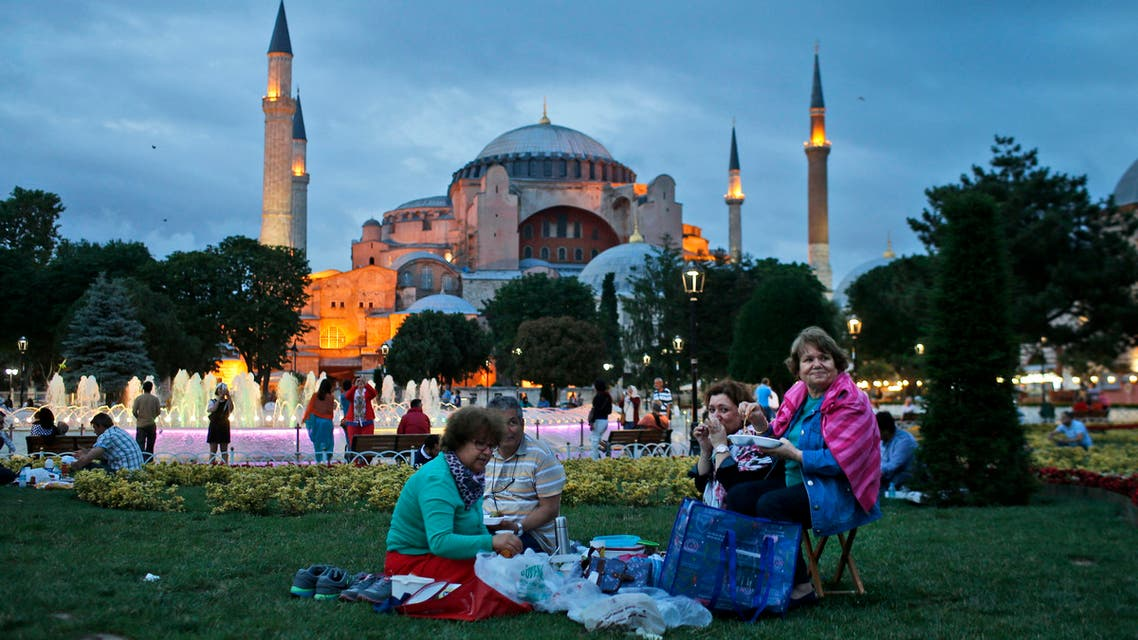 People break their fast backdroped by the Byzantine-era Hagia Sophia, in the historic Sultanahmet district of Istanbul, Turkey, Thursday, June 18, 2015. (AP)