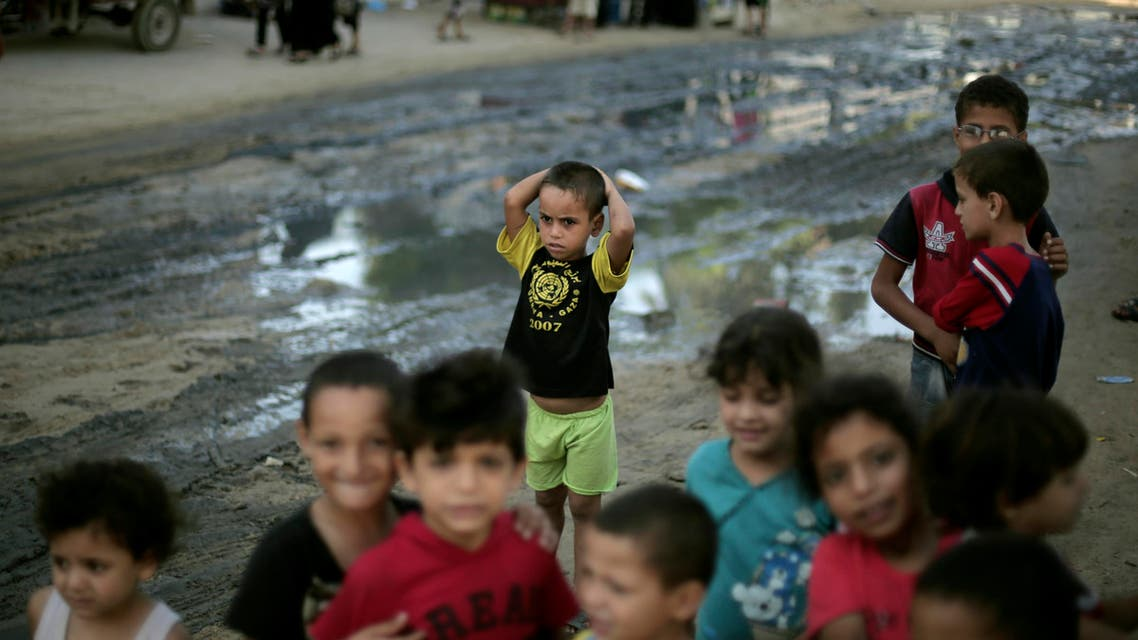 In this Wednesday, Sept. 3, 2014 photo, Palestinian children play outside a U.N. school in Gaza City where they live after their houses were destroyed by Israeli strikes. AP