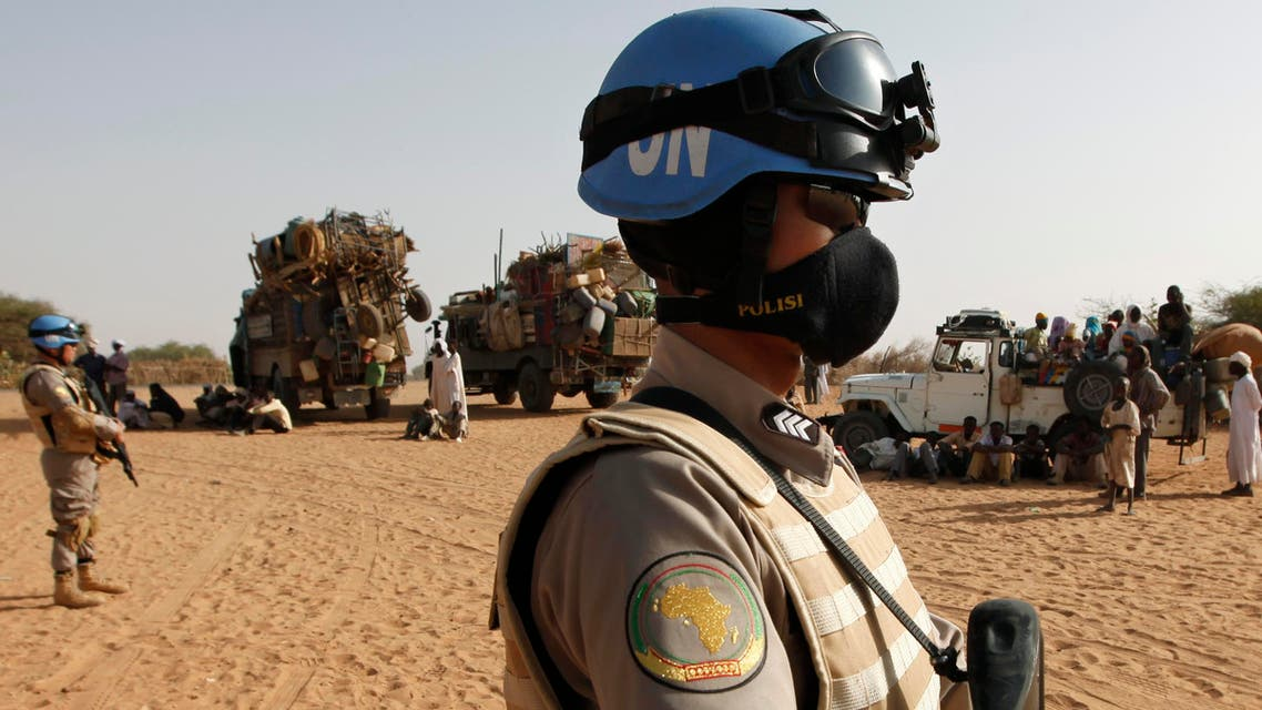 Two UNAMID peacekeepers patrol by trucks loaded with new arrivals of displaced Sudanese at Zamzam refugee camp, outside the Darfur town of al-Fasher, Sudan, Monday, March 23, 2009.
