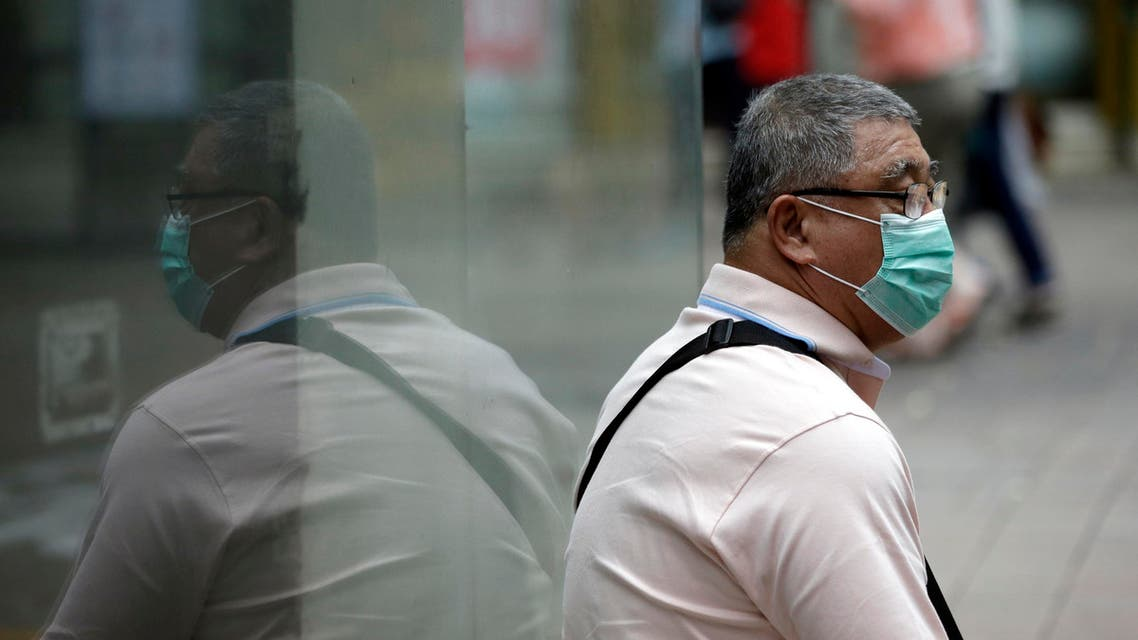 A man wearing a mask as a precaution against Middle East Respiratory Syndrome (MERS) takes a rest at a shopping district in Seoul, South Korea, Thursday, June 11, 2015.
