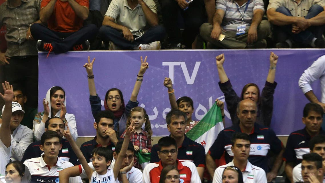 Women among men cheer while following a match of Iran's national volleyball team with the USA during Men's Volleyball World League, at the Azadi (Freedom) stadium in Tehran, Iran, Friday, June 19, 2015.
