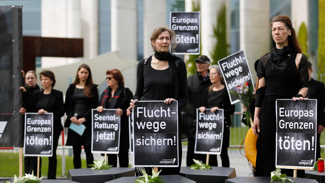 Demonstrators stand behind paperboard caskets display in front of the chancellery during protest of the civil society group 'Campact' against European refugee policy in Berlin, Germany, Friday, May 8, 2015.