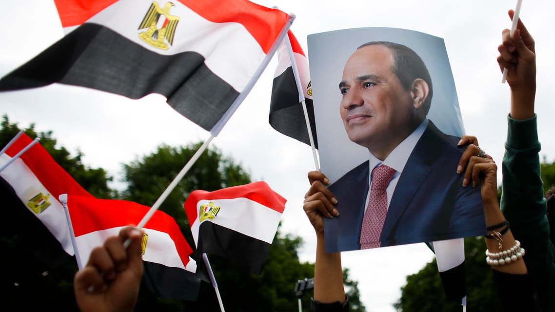 Supporters of Egypt's President Abdel Fattah el-Sissi show posters and wave Egyptian flags prior to his arrival at Bellevue Palace. (AP)