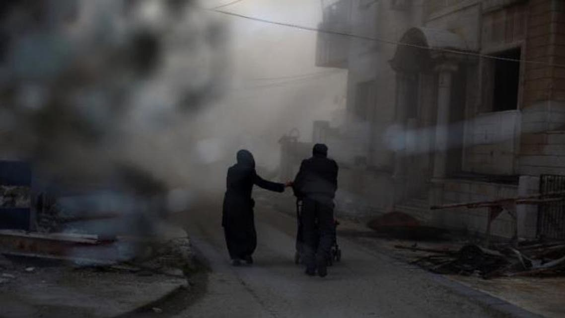 A picture taken from behind broken glass shows a couple pushing a pram as they rush to check their house following an air strike on the rebel-held Damascus suburb of Douma, on February 21, 2015 (AFP Photo/Abd Doumany)
