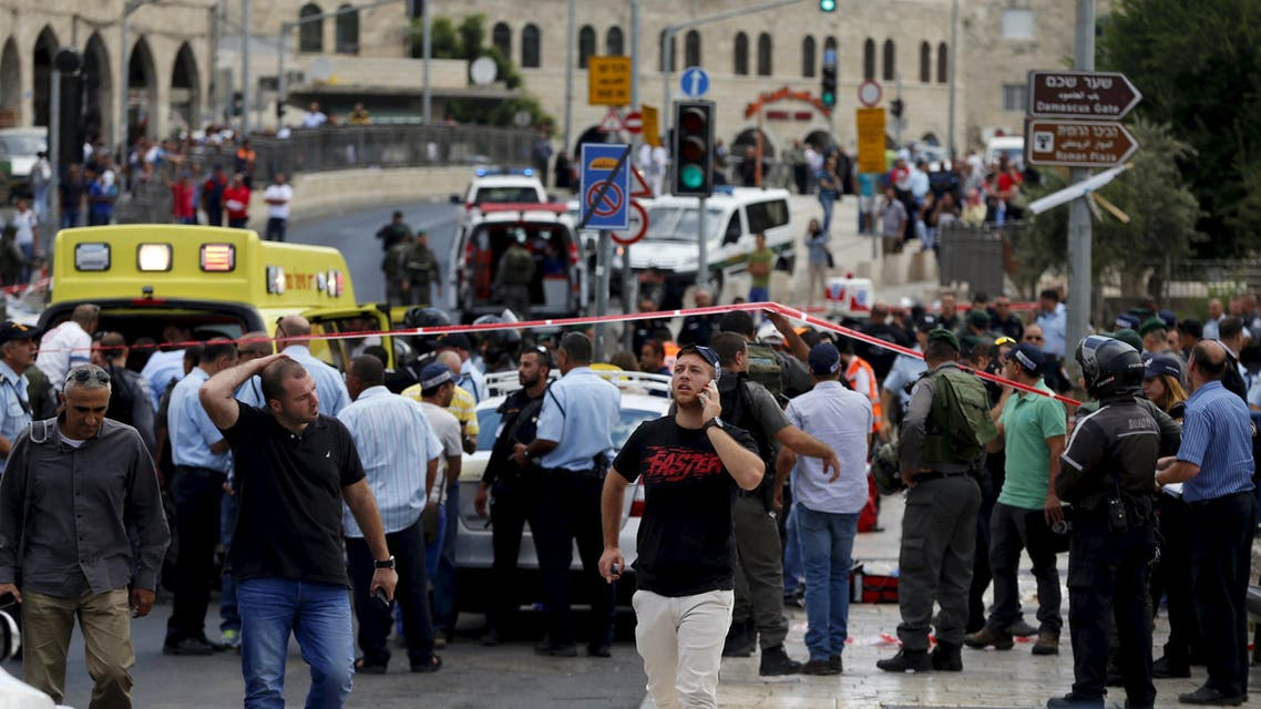 Israeli emergency personnel stand on the scene of a stabbing outside the Damascus Gate in Jerusalem's Old City June 21, 2015.