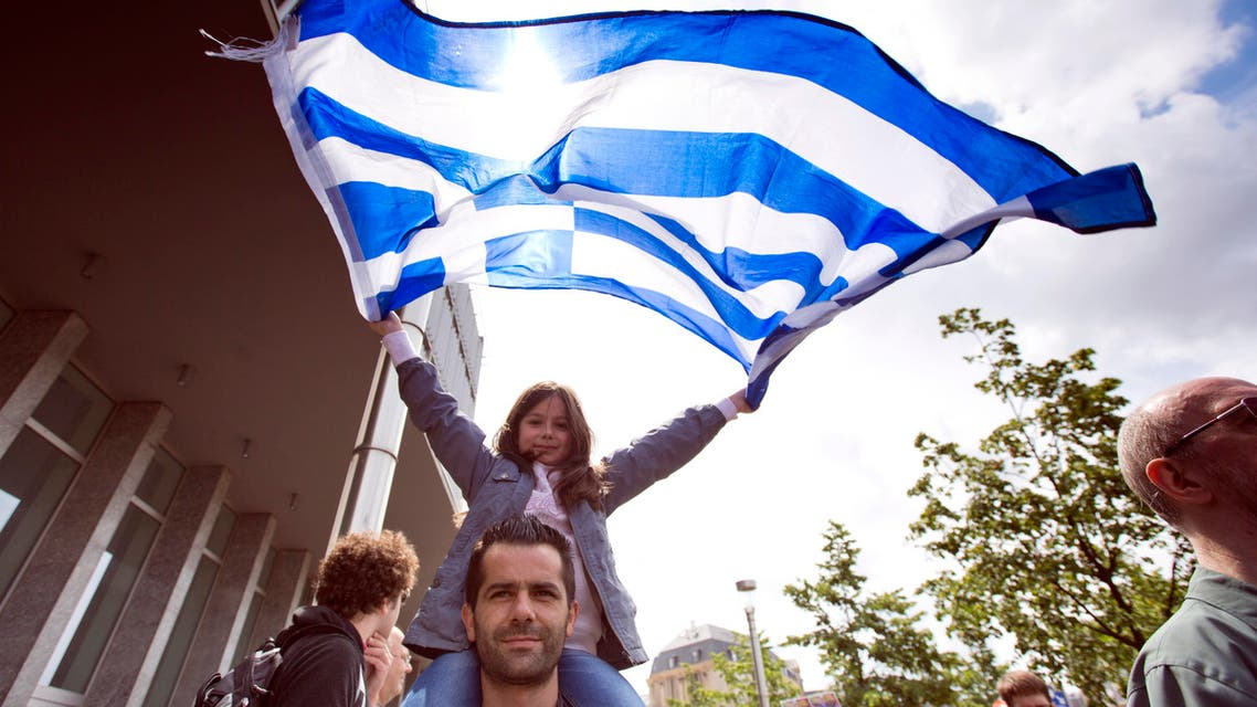 A girl sits on her father's shoulders as she unfurls the Greek flag during a protest march in solidarity with Greece in the center of Brussels on Sunday, June 21, 2015. (AP)