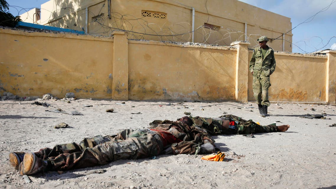 A Somali soldier walks past the bodies of two suspected al-Shabab fighters who were killed while engaging in a car bomb attack in the capital Mogadishu, Somalia Sunday, June 21, 2015.